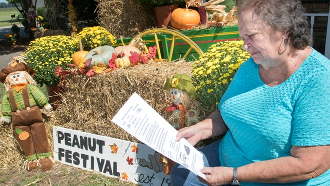 Event organizer Brenda Gabbert looks over a flyer for the annual Peanut Festival in Jay. The Gabbert family started the festival in honor of their daughter, who passed away in 1990.