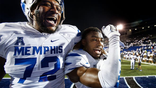 University of Memphis teammates Trevon Tate (left) and Chauncey Lanier (right) celebrate a 34-27 victory over Temple at the Liberty Bowl Memorial Stadium.