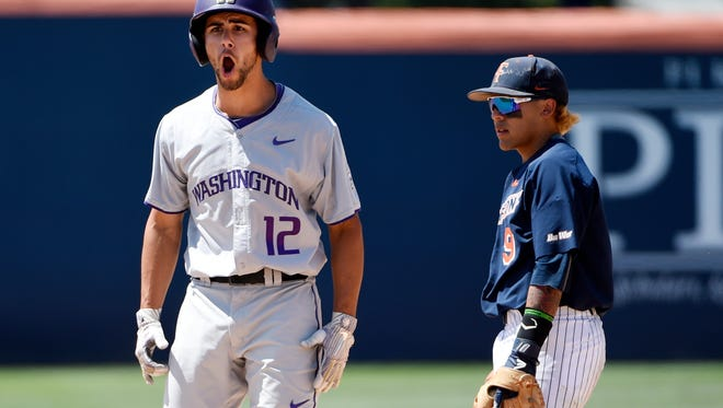 Washington's Kaiser Weiss, left, celebrates his two-run double as Cal State Fullerton's Hank LoForte watches during the ninth inning of Game 1 of an NCAA college baseball tournament super regional Friday, June 8, 2018, in Fullerton, Calif. Washington won 8-5. (AP Photo/Chris Pizzello)