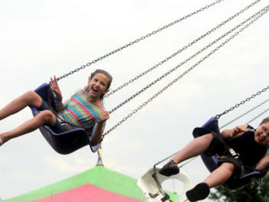 Alyssa Taccino, left, and Frankie Tacinno ride the Swinger at the 2013 Mercersburg Fair.