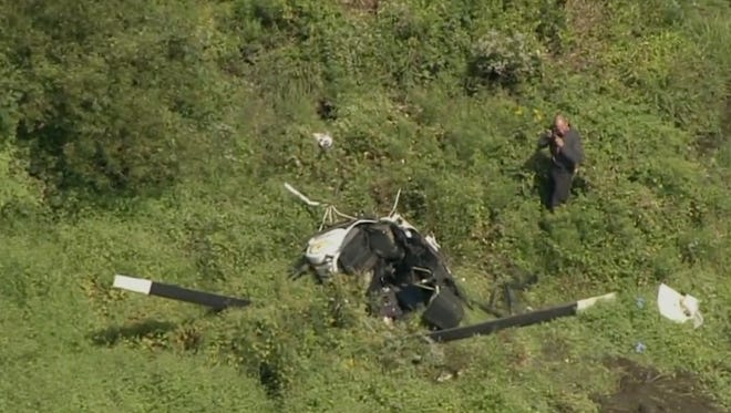 An investigator photographs the scene of a fatal helicopter crash in Medford that killed country music star Troy Gentry. This image is  from aerial video footage taken by NBC 10 News in Philadelphia.