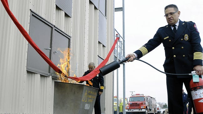 Doña Ana County Fire Chief Robert Monsivaiz keeps a fire extinguisher ready as fire is set to a bright red ribbon to formally open the Doña Ana County Fire and Emergency Services Department's new Las Cruces burn tower in January 2015, where volunteers and paid firefighters now train.