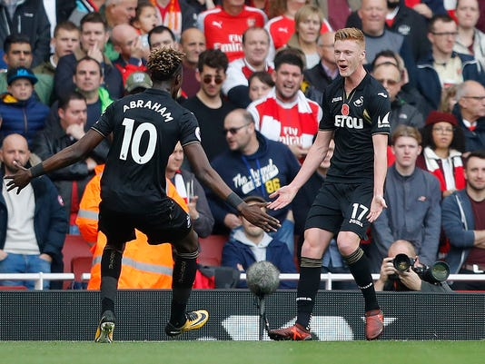 Swansea's Sam Clucas, right, celebrates with teammates after scoring his side's first goal during the English Premier League soccer match between Arsenal and Swansea City at the Emirates stadium in London, Saturday, Oct. 28, 2017. (AP Photo/Frank Augstein)