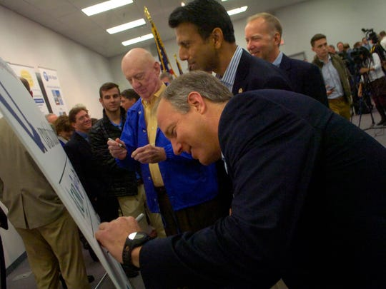 Crest Industries CEO Kenny Robison (center) and his father Tucker Robison (left) and brother Scott Robison (right) along with Gov. Bobby Jindal sign a poster after announcing an expansion in 2013.