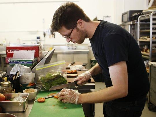 Cody Ricks prepares a sandwich at The Downtown Farm
