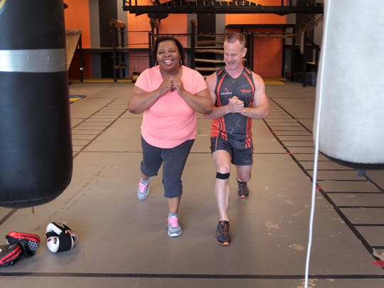 Indianapolis Star editor Leisa Richardson, left, does lunges as she works out with Todd Beattie at the Downtown Boot Camp.