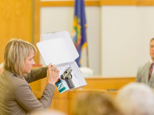Deputy State's Attorney Heather Brochu shows the jury The 9mm pistol that Matthew Webster is accused of using to gun down Anna Alger in 2013. Vermont State Trooper Eric Patno, who seized the gun from Webster, looks on.