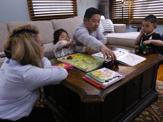 Lada Xiong-Vang, left, looks on while her husband Pao Vang plays with her 2-year-old son Jacobi and 4-year-old daughter Zendaya Monday, May 21, 2018, at their house in Wausau, Wisc.
