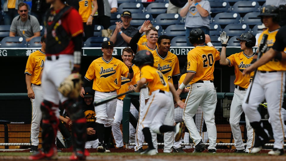 Iowa players welcome Austin Guzzo (20) to the dugout