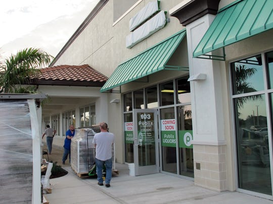 Workers move supplies Thursday, March 2, for the new Publix Liquors store in the Neighborhood Shoppes at Orangetree at Immokalee Road and Randall Boulevard in Golden Gate Estates.
