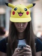"""Donning a Pikachu hat, a girl looks for Pokémon in Madrid on July 28, 2016. A girl sporting a """"Pikachu"""" hat uses the Pokemon Go application on her mobile as she participates in a mass gathering in Madrid on July 28, 2016."""