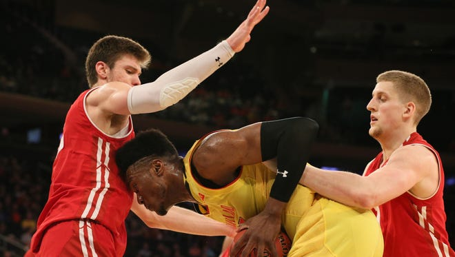 Ethan Happ and Brevin Pritzl of Wisconsin harass Maryland's forward Bruno Fernando with tight defensive pressure during the second half of their Big Ten Tournament second-round game on Thursday afternoon in New York.