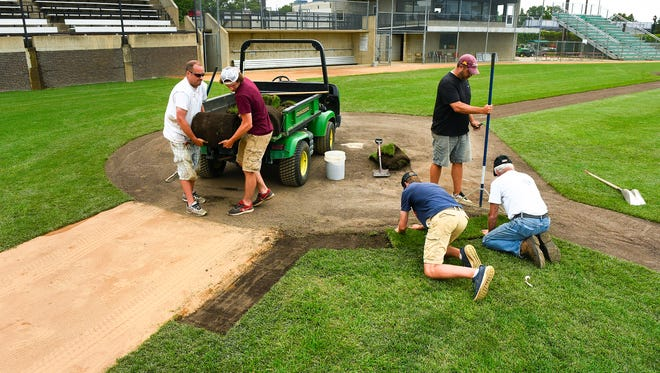 Grounds crew members are busy at the Municipal Athletic Complex Monday, June 12, replacing areas of worn turf on Dick Putz Field. The grounds crew is busy getting ready for the state Class 2A baseball tournament.