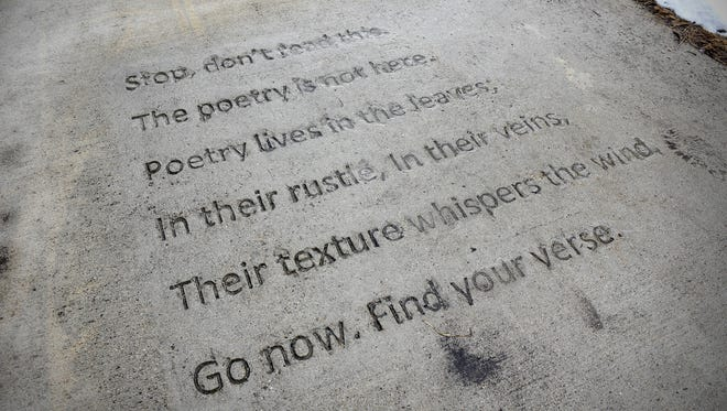 A verse is written into a sidewalk near Wilson Avenue Northeast Friday, March 30, 2018, in St. Cloud.