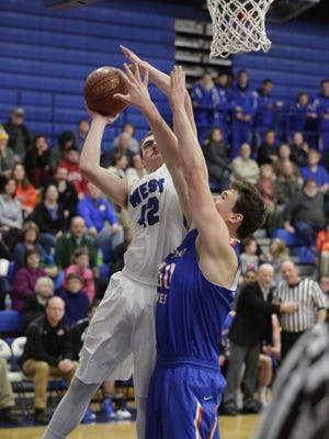 Oshkosh West's Derek Kroll puts up a shot over Jack Flynn of Appleton West on Friday in Oshkosh.