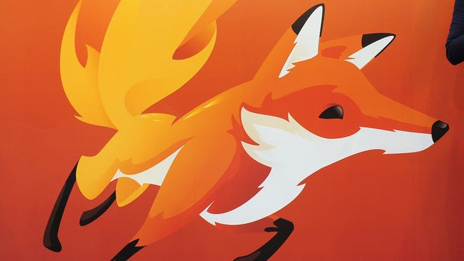 A woman looks at her mobile phone as she stands in front of a poster of Mozilla Firefox in 2013.