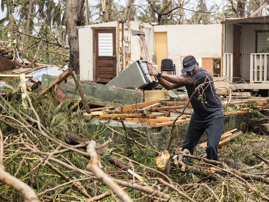 A resident clears debris, Friday, days after Hurricane