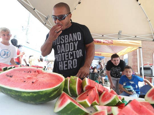 Harry Brown enjoys some of the fruits of his labor as he works to feed the masses during Monticello's 68th annual Watermelon Festival on Saturday, June 16, 2018.