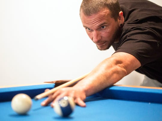 Erik Gunn lines up a shot on the pool table in his Pleasure Ridge Park home. Gunn enjoys the perks of home ownership for the first time having purchased the house in January.