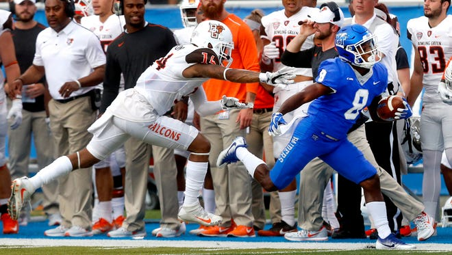 MTSU's Ty Lee (8) runs the ball as Bowling Green's Janarvis Pough (14) moves in for the tackle during the game, on Saturday, Sept. 23, 2017, at MTSU