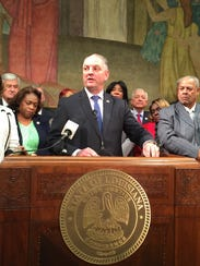 Gov. John Bel Edwards, surrounded by lawmakers, declared