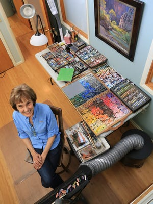 Arlene Braithwaite poses in her Cedar City studio with her art and the pastels she uses to create it.