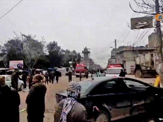 An image grab taken from a video published by Hawar News Agency (ANHA) on Jan. 16, 2019, shows people gathered at the scene of a suicide attack in the northern Syrian town of Manbij. The suicide attack targeted US-led coalition forces in the flashpoint northern Syrian city of Manbij.