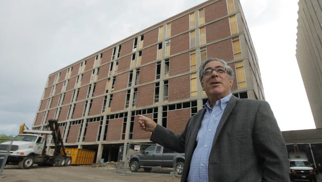 In this June 24, 2010, photo, developer Larry Glazer gestures toward a building to be demolished on Alexander Street in Rochester. Glazer and wife, Jane, were aboard their small plane when it crashed Friday off the coast of Jamaica.