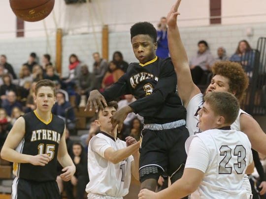 Athena's Nigel Scantlebury, center, draws in a trio of Arcadia defenders then kicks the ball out to the wing for a three point attempt.