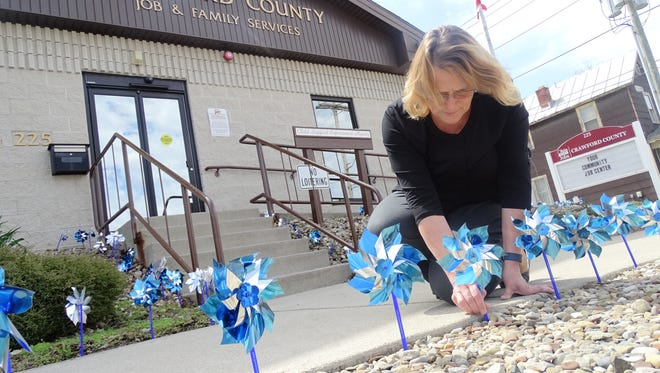 Cassandra Holtzmann places one of 334 pinwheels outside Crawford County Job and Family Services on Wednesday to representing one of the 334 cases of child abuse investigated in the county in 2016.