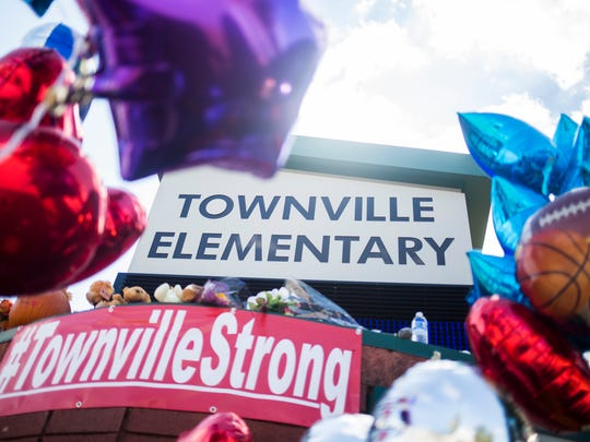 Dozens of balloons, cards, stuffed animals, flowers, and candles have been placed around the Townville Elementary sign in front of the school to create a memorial on Monday, October 3, 2016 in Townville.