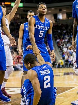 Kentucky Wildcats guard Andrew Harrison (5) helps up his brother Kentucky Wildcats guard Aaron Harrison (2).