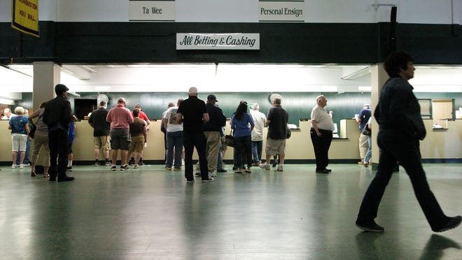 Horse racing fans place their bets on races at Monmouth Park in Oceanport in May. (file photo)
