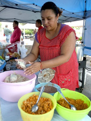 Claudia Falcon makes gorditas at Claudia's Kitchen during The Original Independence Farmers Market on Saturday, May 30, 2015, in Independence, Oregon.