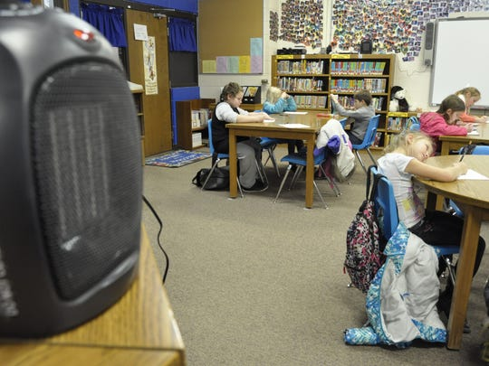 Small space heaters keep things warm in the library at Amanda Gist Elementary School on Wednesday as students study after a heating unit failed a few days ago. School officials hope a new heating unit will be up and running by the time students return from the holiday break.