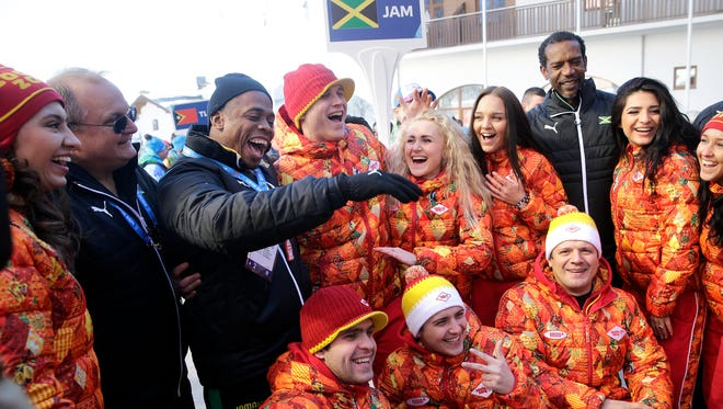 Members of Jamaican Olympic team, including bobsled brakeman Marvin Dixon, third from left, and coach Paul Skog, second from left, pose with the Choir of Siberia after a welcome ceremony at the Mountain Olympic Village.