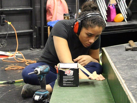 """Theater major Julia Rivera, 19, carefully checks over her work as she helps with the set for """"Paragon Springs."""" Rivera, a Florida SouthWestern State College student, is a cast member. She and other students will perform the play next month."""