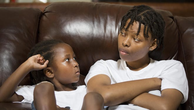 Vincent DuBose, 4, and his sister, Teaila Williamston, 15, listen to DaShonda Reid talk about their father, Samuel DuBose. DuBose was fatally shot on July 19 during a routine traffic stop in Mt. Auburn by former University of Cincinnati police officer Ray Tensing. He has since been indicted for murder. Reid is Vincent's mom and step-mom to Teaila, whose mother died from breast cancer last year.