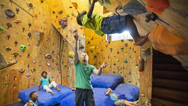 """Gregg Eichhorn, plays with five of his eight children in a rock climbing addition he built a year ago behind his home in Price Hill. He and his wife, Katie, have seven adopted children, with the eighth adoption pending. Seven have special needs. They call the room, """"The Crux"""", which is a rock climbing term for the hardest part of the climb."""