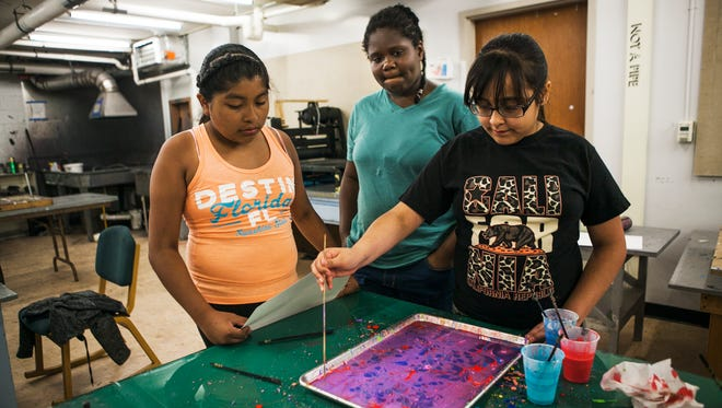June 22, 2017 - (L-R) Belinda Morales, 11, and Sydney Scott, 12, watch Brianna Saucedo, 11, as she makes a paper marbling print during a printmaking class led by instructor Gulcan Demirtas, not pictured, during the Dixon Art Camp at the University of Memphis on Thursday. The free summer camp marks the third time Dixon Gallery and Gardens has partnered with U of M to offer the opportunity to students, from first through eighth grade, whose families live in neighborhoods around Dixon and the university.