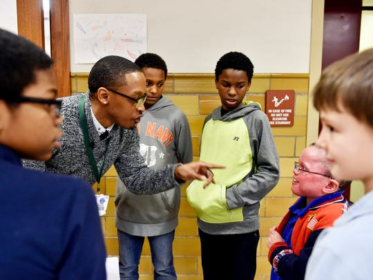 Martin Library site coordinator Diaz Woodard, second from left, assigns roles for a skit to teach different aspects of respectful behavior. From left: fifth-grade student Antonio Riley, sixth-grade student T'Kwon Banks, seventh-grade student Diante Farrell, fourth-grade student Elio Figueredo and third-grade student Trey Gunter.