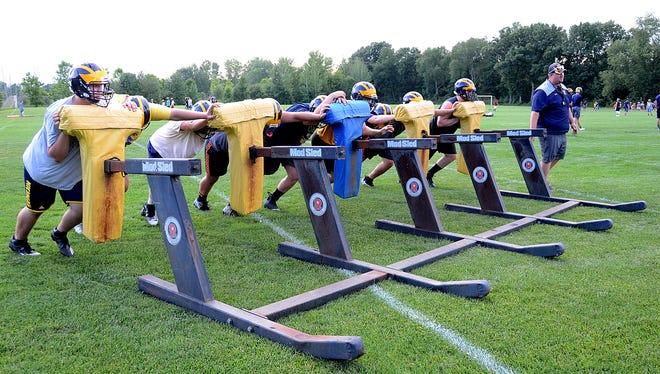 Hartland football players prepare for their season opener Thursday at Westland John Glenn.