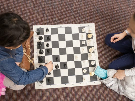 Youths play chess in this file photo.
