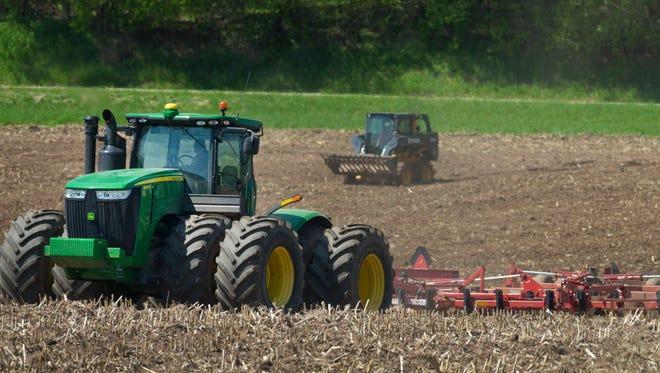 Farmers perform fieldwork Tuesday in Waupaca.