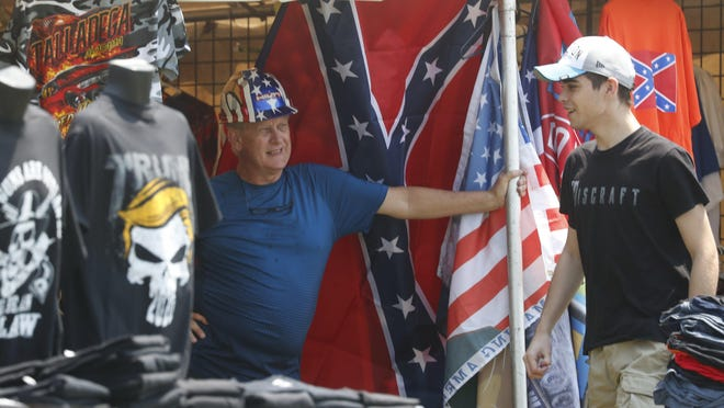 "Ed Sugg, left, talks with a customer Sunday at his merchandise tent near Talladega Superspeedway. NASCAR has banned the Confederate flag on its property, but Sugg said the flags were selling well for him. ""I don't think anybody really connects it to any kind of racism or anything,"" he said. ""It's just a Southern thing."""