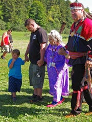 Four generations of the Stevens Family take part in traditional dancing at the 2015 Wabanaki Confederacy Conference in Shelburne Vermont. Chief Don Stevens wears regalia including ribbon shirt, finger-woven sash, wampum choker and headband. His mother Margaret Stevens wears a traditional woman's ribbon dress. Donald Stevens III and his son Shadow Stevens wear everyday clothes.