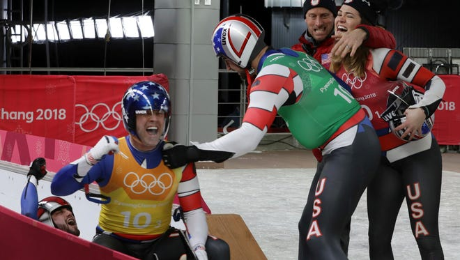 Summer Britcher, in red, Chris Mazdzer, in green, Matt Mortensen and JaysonTerdiman of the United States react in the finish area after the luge team relay at the 2018 Winter Olympics in Pyeongchang on Feb. 15. The USA relay team was in first place after its run, but ultimately finished fourth after the final three teams finished ahead.