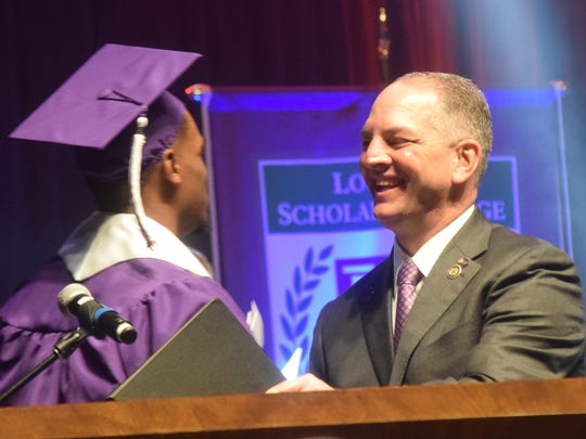At May commencement Northwestern State University's student-athlete Jalan West (left) introduces Gov. John Bel Edwards as guest speaker. Northwestern is receiving about a $500,000 cut in state funding this year.
