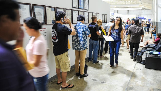 Customers line up to conduct transactions at the Treasurer of Guam window in the Department of Revenue and Taxation in Barrigada Heights on Friday, April 15.