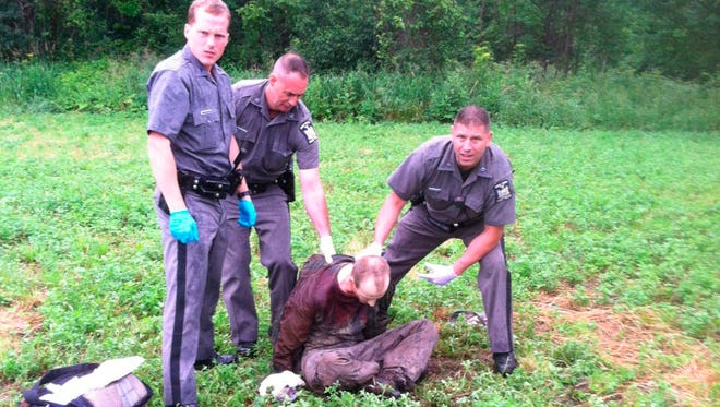 Police stand over David Sweat after he was shot and captured near the Canadian border on June 28, 2015, in Constable, New York.